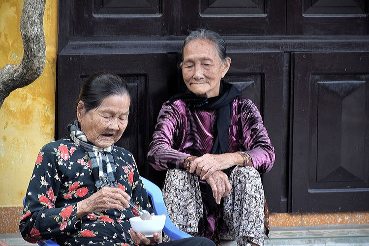 Two ladies having a light lunch in a street of Hội An Elderly Ladies In Vietnam Hoi An Streets Hoi An, Vietnam Old People Eating In The Street In Vietnam Rice Bowl Meal Two Asian Ladies Having Lunch