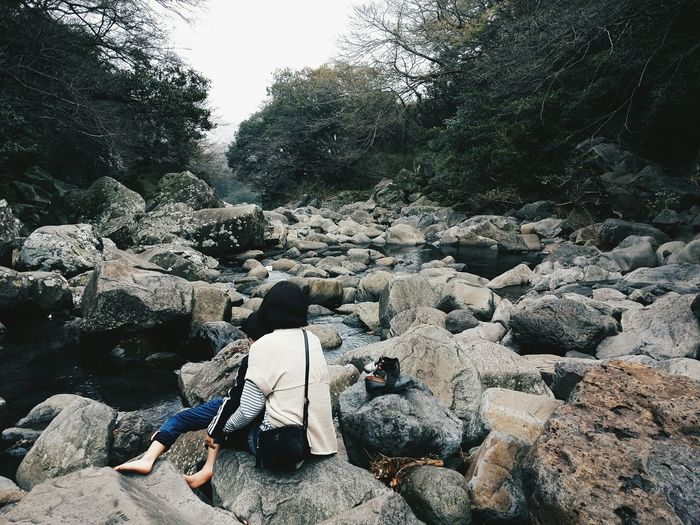 Rear view of woman sitting on rock at riverbank in forest