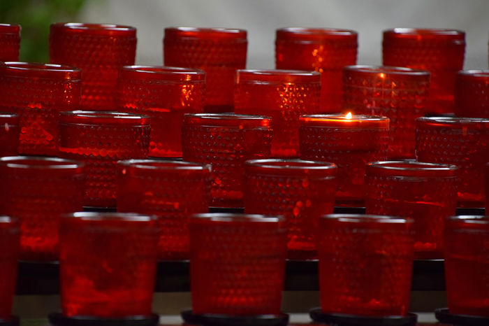 Candles in red glass holders in church Arrangement Beacon Beautifully Organized Burning Candlelight Candles Catholic Christianity Church Close-up Glass Holder Hope In A Row Large Group Of Objects Light Order Perspective Place Of Worship Prayer Red Religion Religious  Sconce Temple