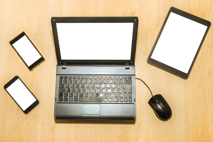 Flat lay of a business desktop with accessories: a computer, a keyboard, a monitor, a mouse, a tablet, a smart phone, a pen holder, a desk phone, a hard disk. Flat lay of a business desk with mobile phones, tablet pad, and notepad with pen and paper. Blank screens and paper for copy space aerial view of a technology table with tools: a computer laptop, mobile phones, tablet and mouse. blank white screen for copy space. Blank white screens for copy space Desk Desks From Above Desktop Mobile Phone Office PC TAB Tablet Work Aerial Calculator Computer Flat Flat Lay Key Keyboard Mobile Monitor Note Notebook Paper Pens Table Tablets Telephone