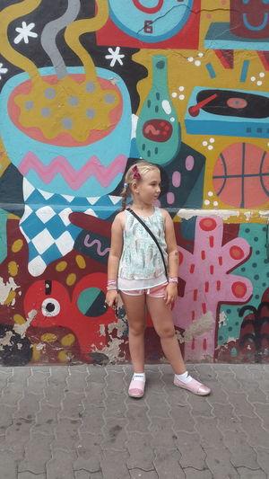 Full length of smiling girl standing against wall