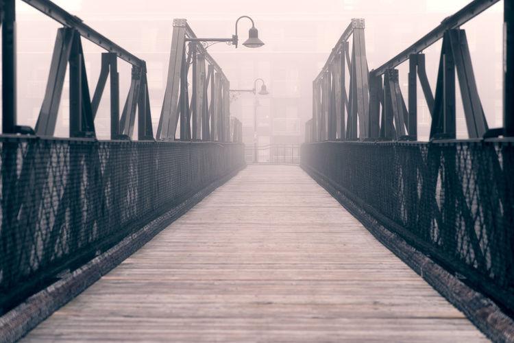 Empty footbridge against sky