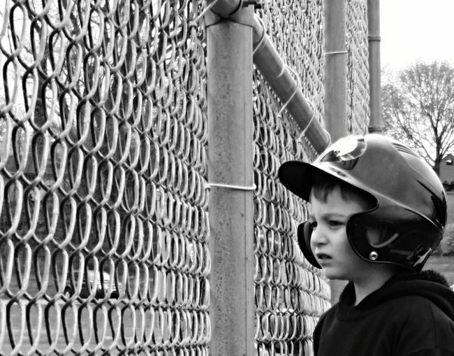 Close-up of boy wearing baseball helmet by chainlink fence
