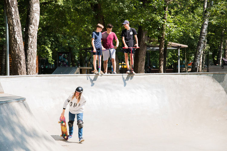 Full Length Tree Casual Clothing Togetherness Group Of People Leisure Activity Child Men Day Plant Real People Nature Lifestyles People Males  Boys Skateboard Park Friendship Bonding Childhood Outdoors Positive Emotion Teenager Teenage Boys