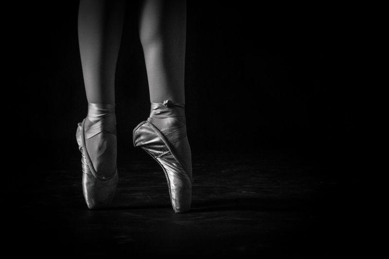 Low section of ballet dancer against black background