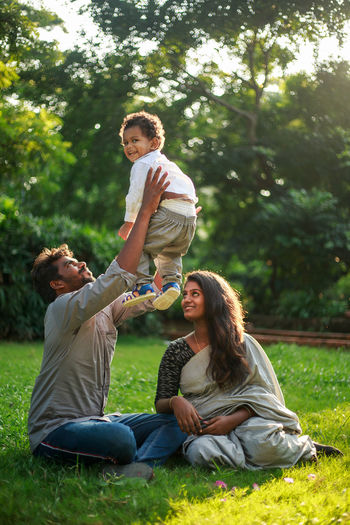 Family with a child sitting on grass in a park
