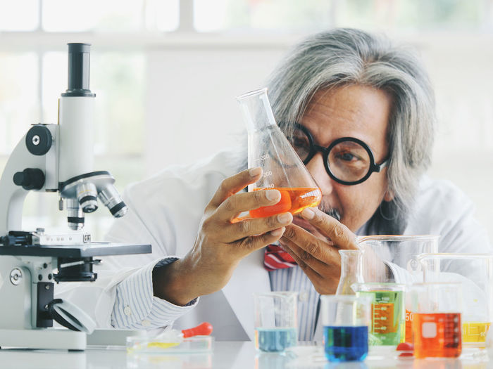 Healthcare And Medicine Research One Person Gray Hair Science Laboratory Headshot Glasses Scientific Experiment Indoors  Eyeglasses  Front View Portrait Senior Adult Education Adult Mature Adult Holding Microscope Medical Research Lab Coat Hairstyle White Hair