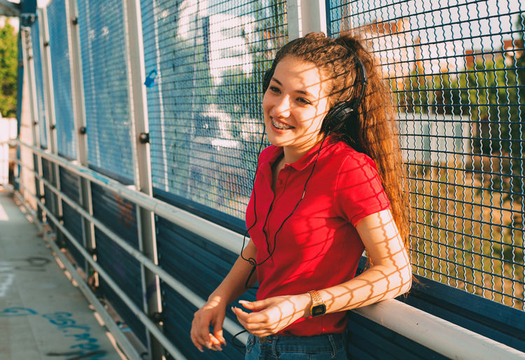 Close-up of smiling girl standing against fence outdoors