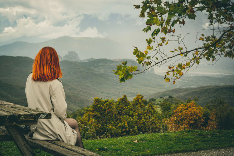 Woman sitting on picnic table against mountains