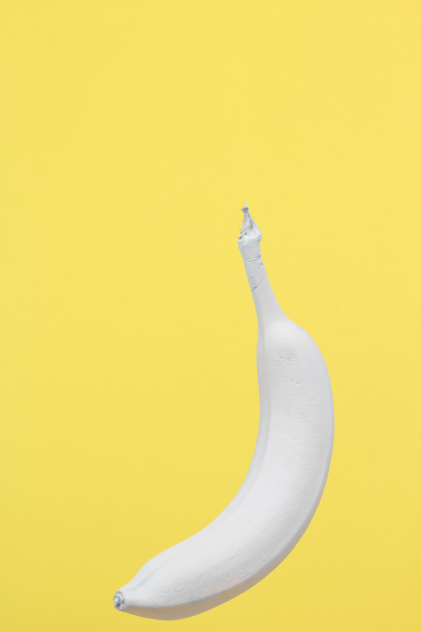 CLOSE-UP OF BANANAS ON YELLOW BACKGROUND