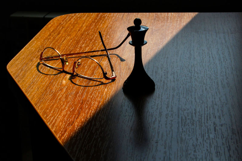 Chess piece by eyeglasses on wooden table