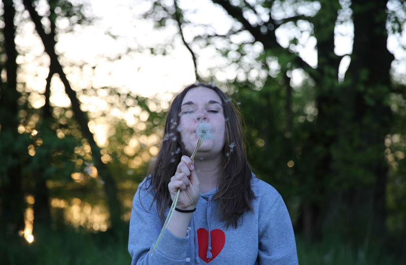 Teenage girl blowing bubbles standing against trees