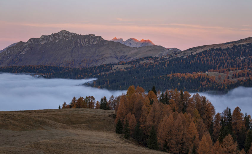 Scenic view of lake by mountains against sky during sunset in dolomites mountains