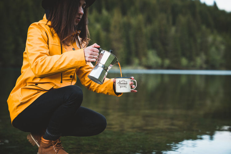 Woman pouring coffee in mug while crouching by lake