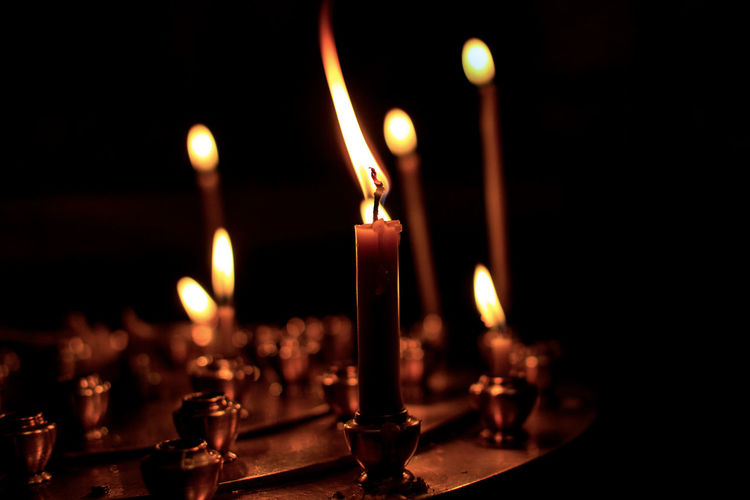 Close-Up Of Burning Candles In Darkroom