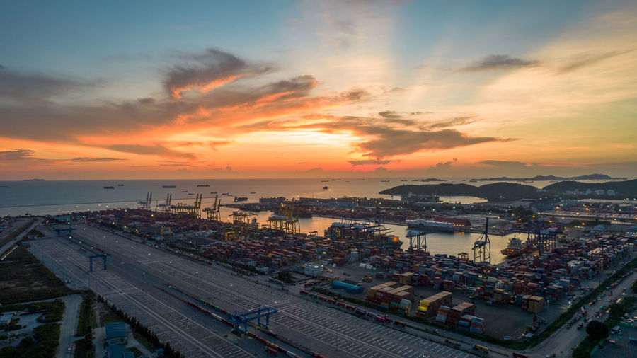 Aerial view of sunset sky at international cargo sea port.