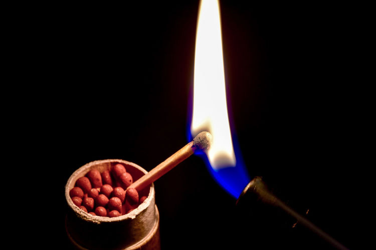 Close-up of igniting matchstick against black background