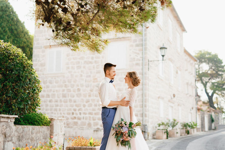 Young couple embracing while standing on street