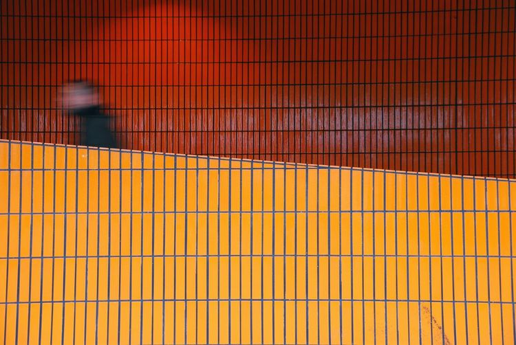 Blurred motion of man walking by tiled wall