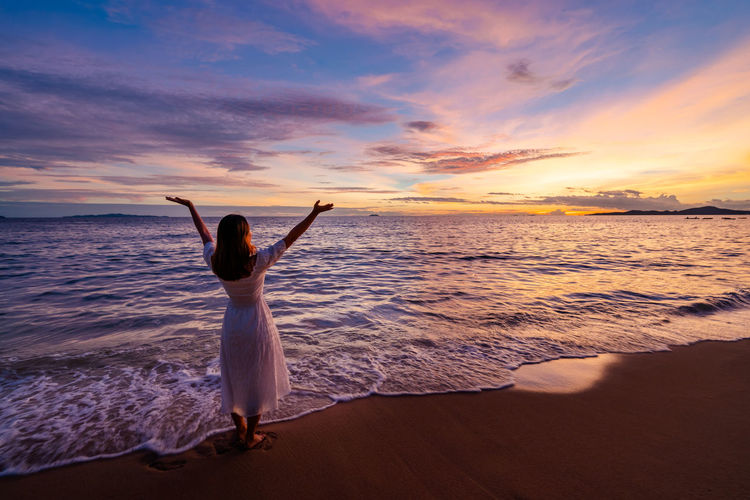 Rear view of woman looking at sea against sunset sky