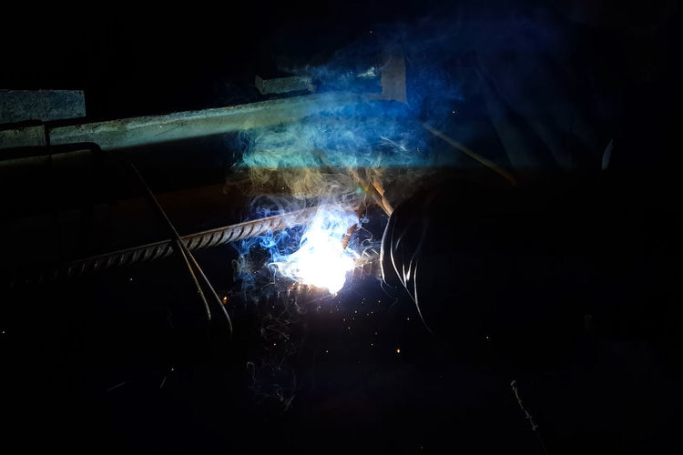 Burning Smoke - Physical Structure Heat - Temperature Motion Indoors  Dark Fire Welding Real People Men Nature Flame Sparks Illuminated Blurred Motion Fire - Natural Phenomenon Glowing Night People Metal Industry