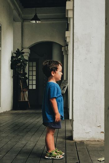 Side view of boy standing outdoors