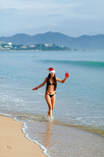 santa girl with gift box on beach in tropics. Christmas eve in tropics 2018 EyeEm Best Shots Gift Box Happy New Year Around The World New Year Santa Claus Unpacking Active Beach Bikini Christmas Decoration Chrsitmas Gift Lifestyles Present Real People Red Box Sea Sexygirl Sexywomen Tropical Tropical Climate Young Adult Young Women