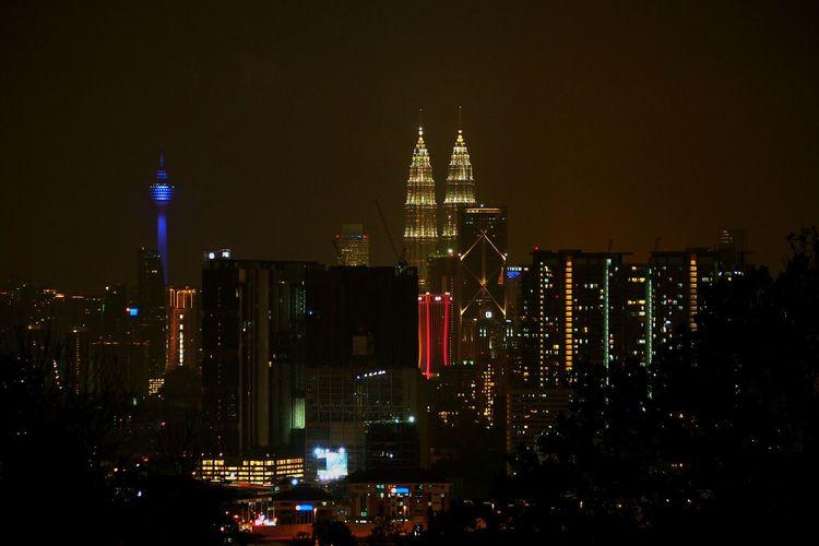 Petronas towers and menara kuala lumpur tower in illuminated city against sky at night
