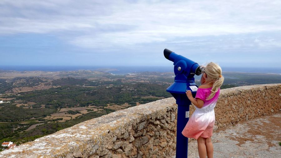Girl looking through coin-operated binoculars against sky