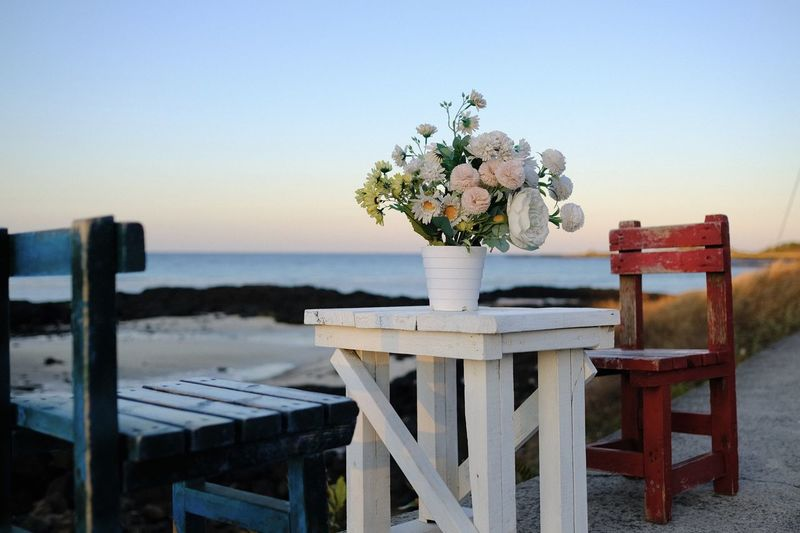 Flower vase on table by sea against clear sky