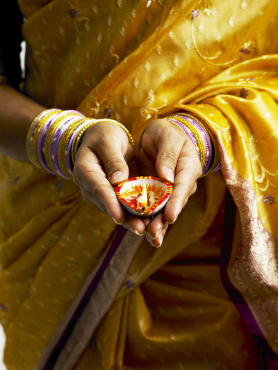 close up of indian woman with traditional clothing holding oil lamp during deepavali Celebration Diwali Ethnicity Flame Indian Woman Traditional Clothing Accessory Bangles Celebration Clay Lamp Close-up Deepavali  Festive Of Lights Gold Colored Holding Human Hand Illuminated Life Events Light And Shadow Oil Lamp People Real People Sari Women Yellow