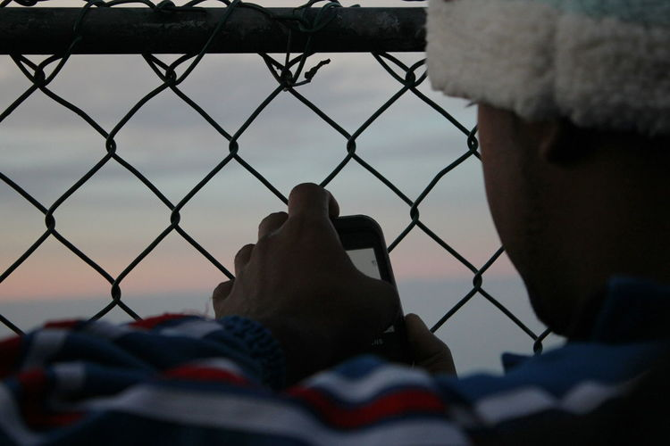 Close-up of hand on chainlink fence against sky