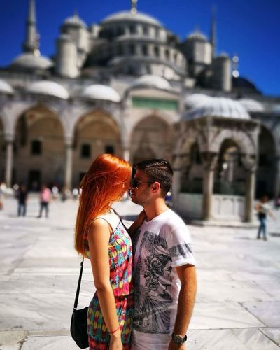 Side View Of Young Couple Standing In Front Of Blue Mosque