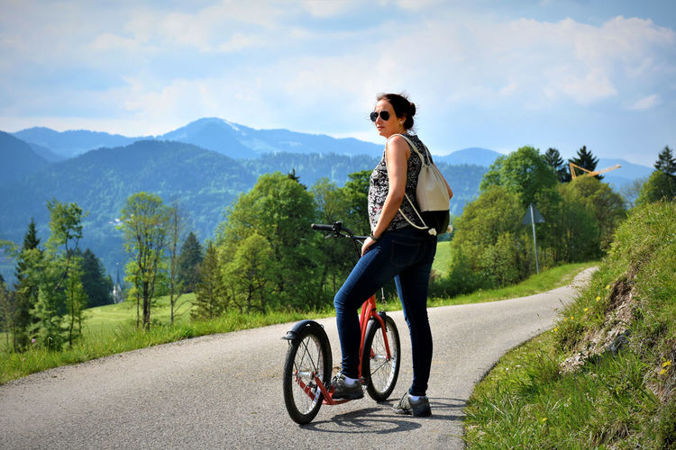 Adventure Bicycle Casual Clothing Cycling Day Full Length Leisure Activity Lifestyles Live For The Story Mountain Mountain Range Nature One Person Outdoors People Real People Riding Road Sky Sunglasses Transportation Tree Young Adult Young Men Young Women