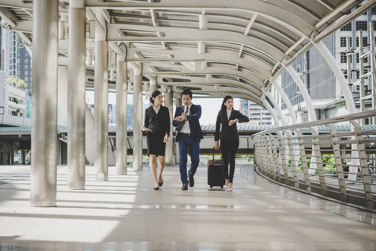 Full length of coworkers walking in office corridor