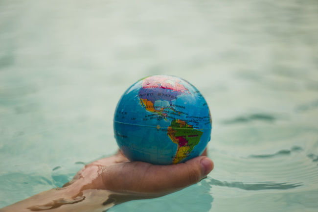 Above close up looking down on hand holding the world over water Hand Holding Hands Map Plant Power Cat Continent Ecology Energy Planet Protection Sustainability Sustainable Sustainable Resources Water World