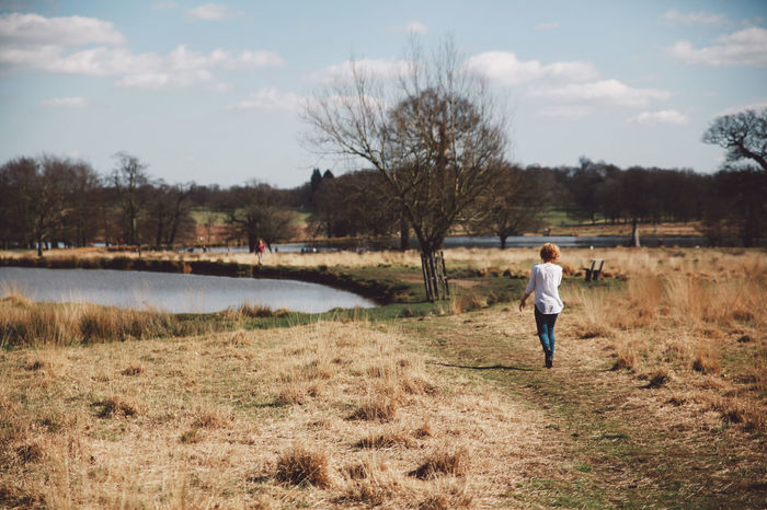 Blonde Blue Jeans Casual Clothing Curly Hair Day Field Full Length Girl Grass Growth Landscape Leisure Activity Lifestyles London Nature Path Pond Rear View Richmond Park, London Sky Spring Tranquil Scene Tranquility Tree White Shirt Lost In The Landscape