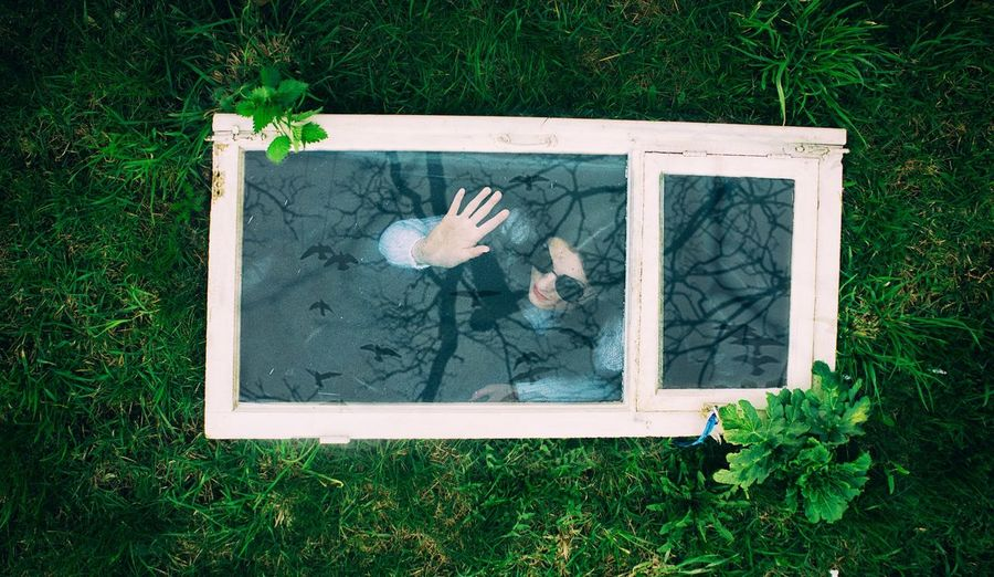 High angle view of woman seen through window frame at field