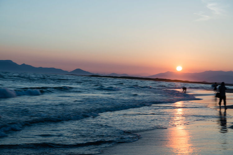 Beach Beauty In Nature Land Leisure Activity Lifestyles Mountain Nature Orange Color Outdoors People Real People Scenics - Nature Sea Sky Sun Sunset Tranquil Scene Tranquility Water Wave