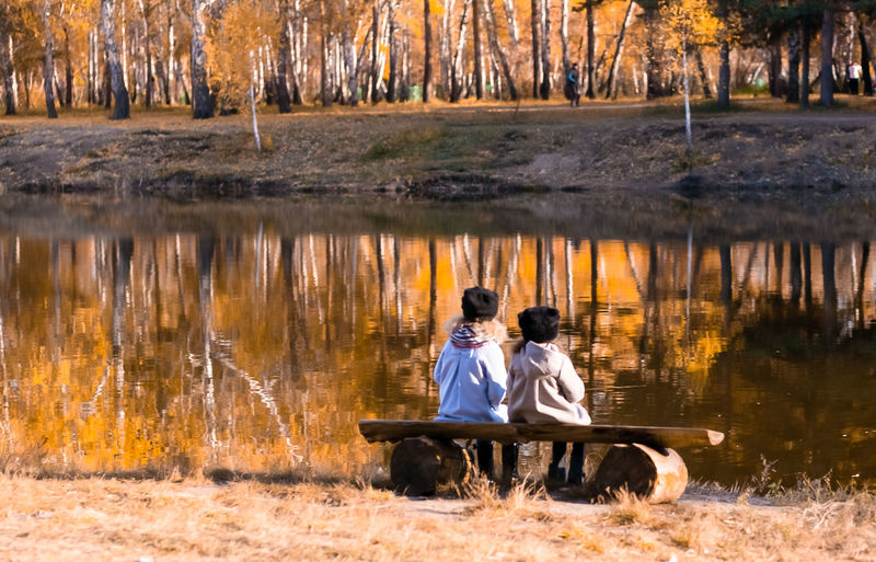 Friends sitting by lake during autumn