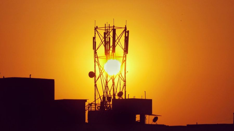 Low angle view of silhouette communications tower against orange sky