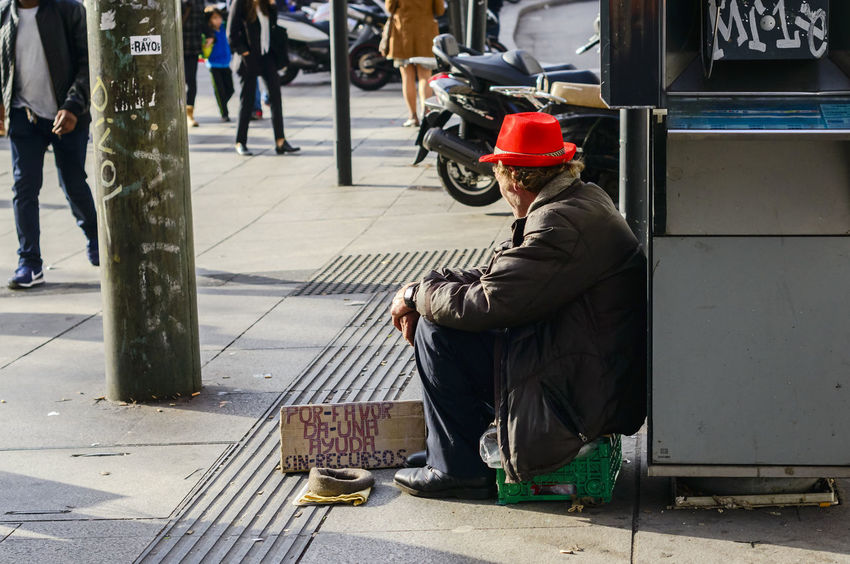 A man sitting on the pavement asking for alms wearing a bright red hat that is reflecting the evening light of the sun. Begging Casual Clothing City City Life Composition Editorial  Hat Lifestyles Man Perspective Real People Red Red Hat Sitting Sitting Street Streetphotography Style Photojournalism