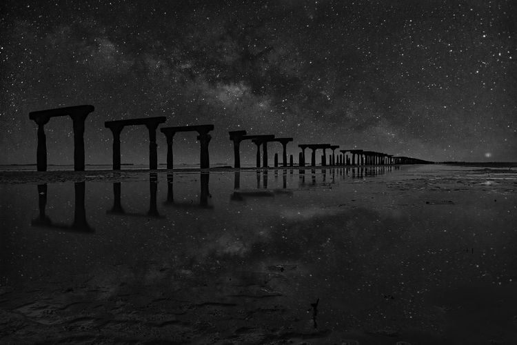Built structure on sea against sky at night
