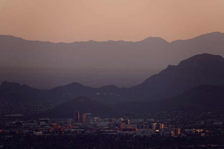 High angle view of downtown tucson and surrounding mountains with orange sunset sky