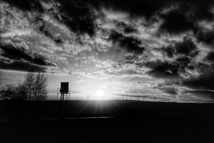 Silhouette of road against cloudy sky
