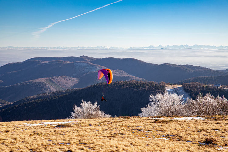 Person paragliding over mountain range against sky
