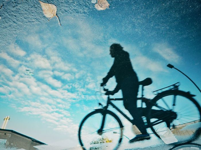 Silhouette man riding bicycle on street