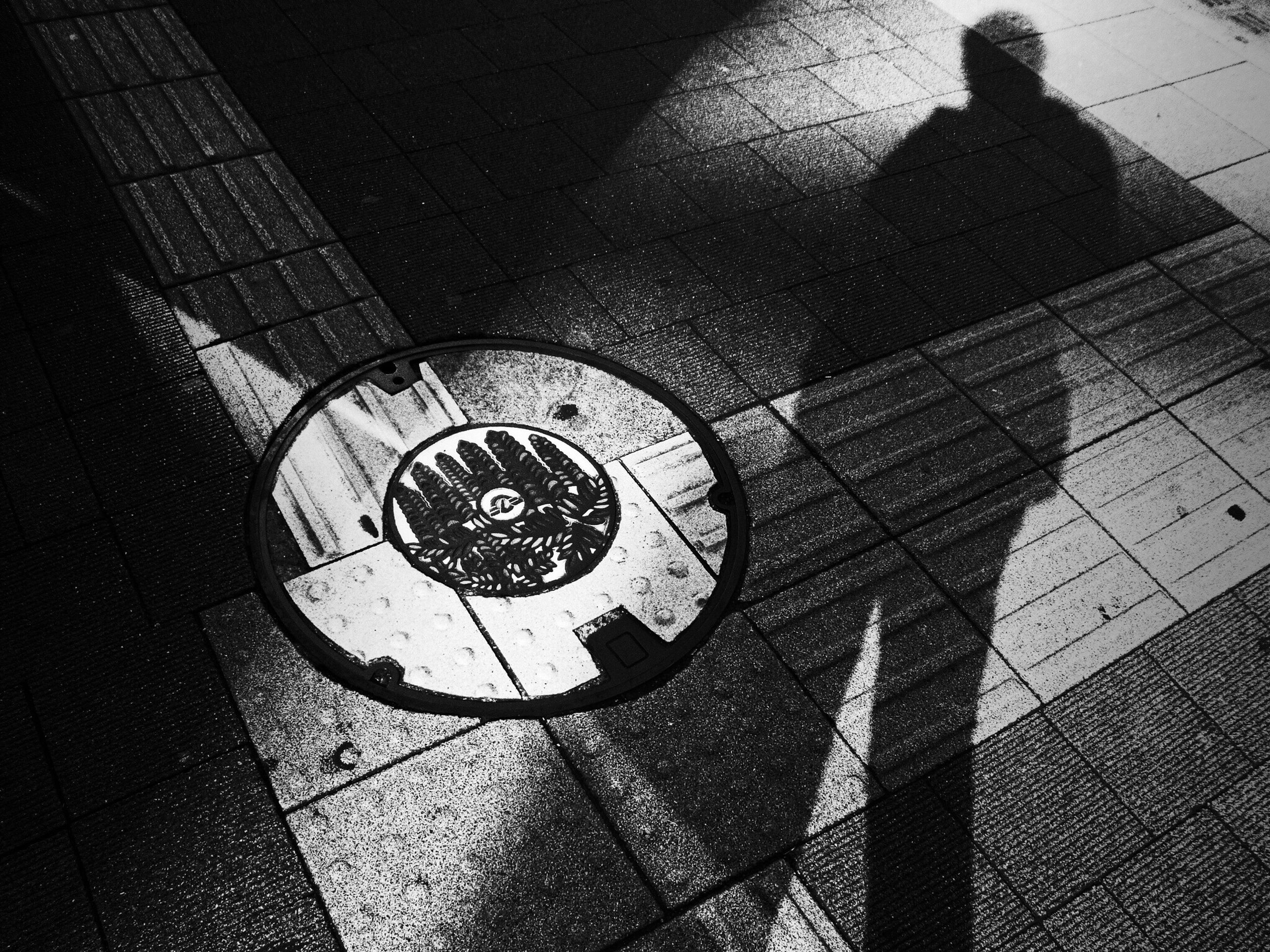 high angle view, street, shadow, communication, transportation, clock, sunlight, time, day, road marking, outdoors, sidewalk, number, road, text, geometric shape, close-up, manhole, guidance
