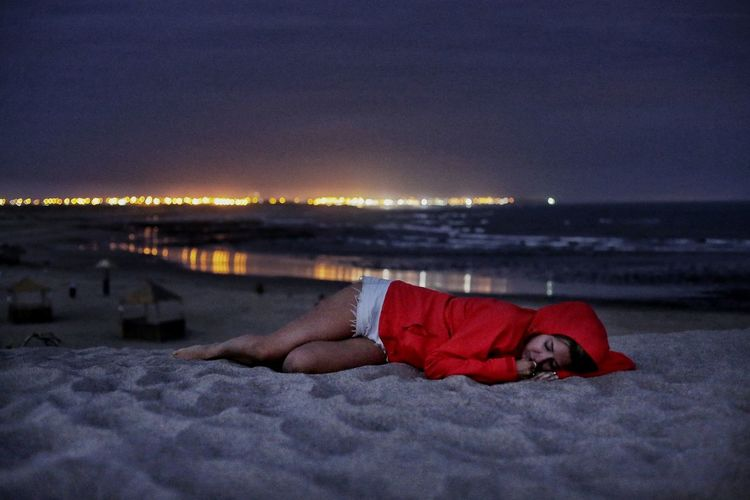 Woman Sleeping At Beach Against Sky During Night