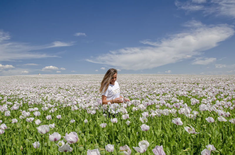 Woman on flowering plants on field against sky
